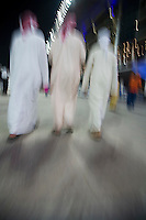 Dubai UAE small group of traditionally dressed Muslim men roaming grounds at Nad Al Sheba