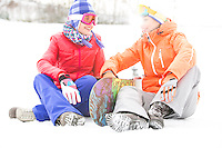 Full length of female friends with snowboard relaxing on snow