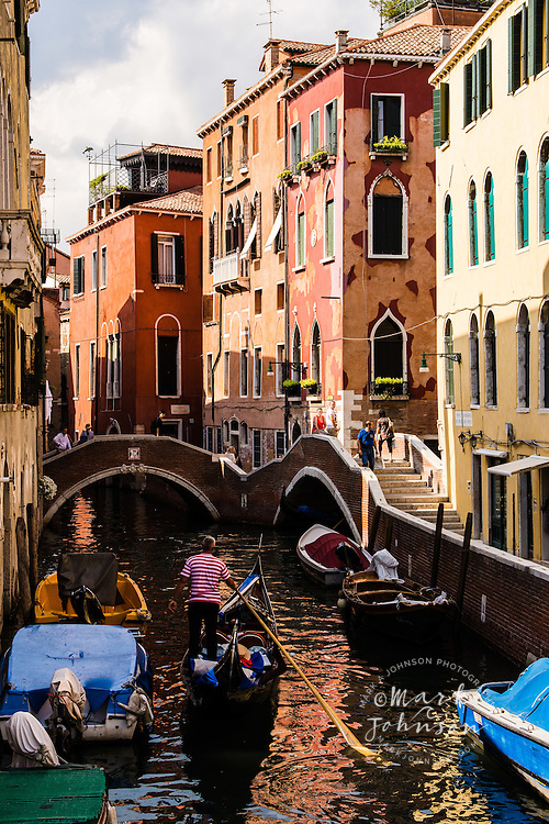 Gondolier paddling gondola, Venice, Italy