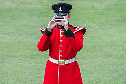 © Licensed to London News Pictures. 31/07/2014. Chichester, UK. A soldier takes a picture on his mobile phone of Hollywood Actor Tom Cruise.  Ladies Day at Glorious Goodwood at Goodwood racecourse in Chichester today 31/07/14. Photo credit : Stephen Simpson/LNP