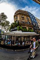 People on electric scooters pass in front of Cafe de Flore. Cafe de Flore (Flora) is a famous café in the Saint-Germain-des-Prés area of Paris, France.