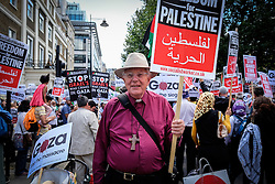 Bishop Richard Llewellin holds aloft a banner protesting against the violence in Gaza. London Aug 2014