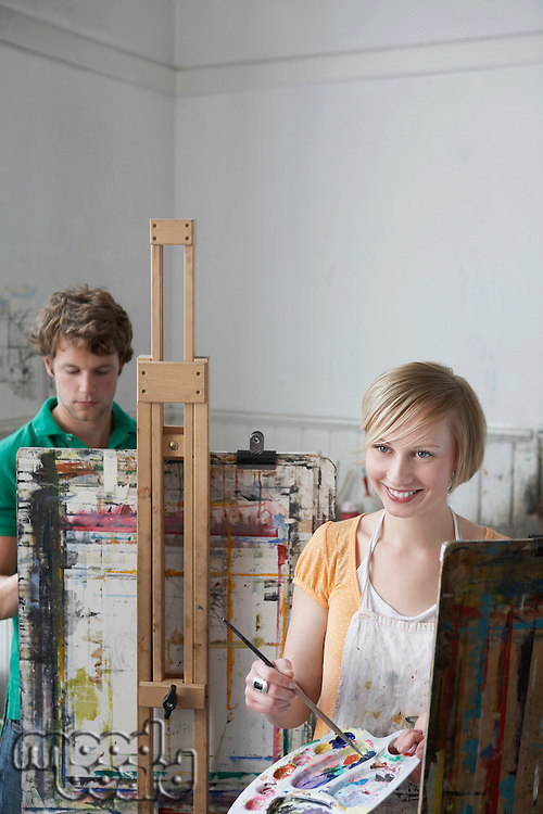2 students painting at easels in art class