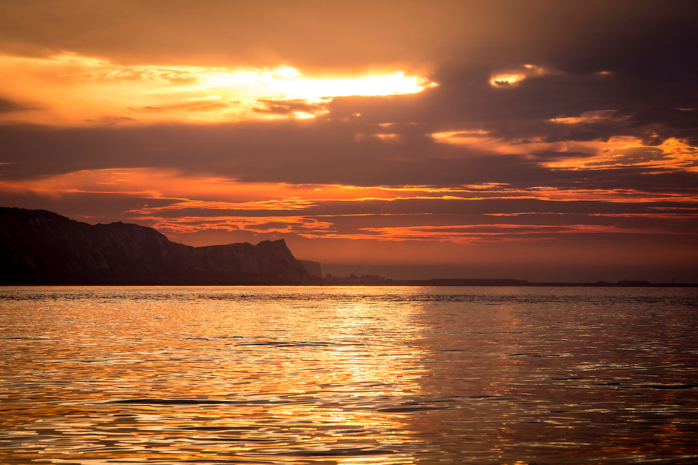 The sun rises over The White Cliffs of Dover and breaks through the clouds in the sky and the sunlight reflects along the calm sea water photographed from a boat in The English Channel off the coast of Folkestone Harbour, Kent, England, United Kingdom.  (photo by Andrew Aitchison / In pictures via Getty Images)