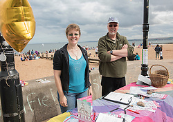 Back for the seventh year - the Portobello Big Beach Busk. Musicians of all sorts just turn up on the Prom, pick a spot from the many chalk circles drawn along the Prom and start playing! Also back for a second year is the sandcastle competition in front of the Baths. Pictured: Kyrsta Macdonald-Scott on the Save Bellfield stall, raising awareness of the community campaugn to save Bellfield Church.   <br /> <br /> <br /> © Jon Davey/ EEm