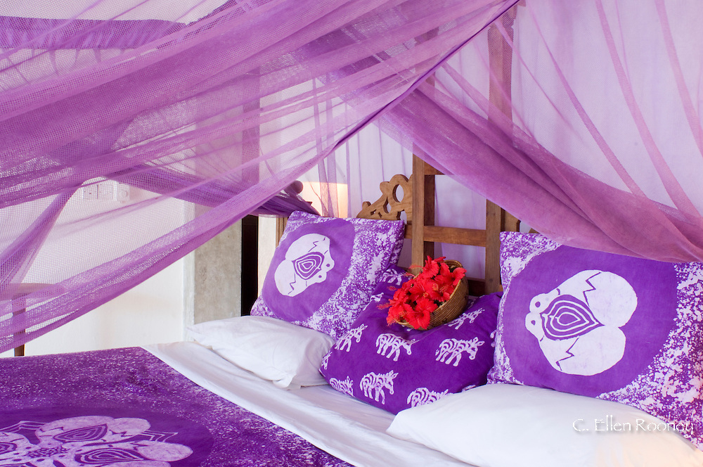 Purple mosquito netting and hibiscus flowers on a bed at the Shooting Star Hotel.  Kiwendwa.<br /> Zanzibar, Tanzania