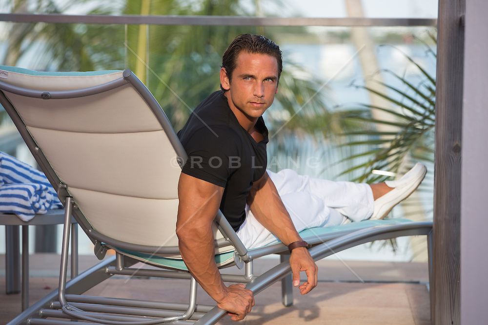 portrait of a good looking middle aged man sitting in a lounge chair at a resort