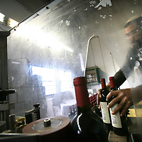 SETTLER'S BOUTIQUE WINE 2009...A Jewish settler collects wine bottles out of a machine after a sticking labels process at Tanya boutique winery in the West Bank Jewish settlement of Ofra, December 2009.