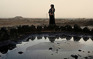 A Uyghur woman standing by a pond of oil spilling from the underground in Kalamayi.  This city is one of the first where oil exploitation started. 20% of China's oil production comes from Xinjiang. Natural ressources such as oil and gas make it a strategic region for China. The oil and petrochemical sector account for 60% of Xinjiang's local economy. However locals complain that the benefits from these resources goes directly to Beijing and does not benefit the region, one of the less developed region in China.