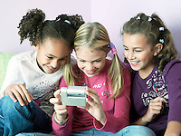 Girls sitting side by side playing with electrical gadget
