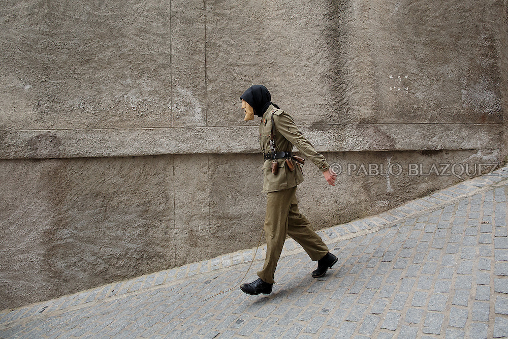 A Machurrero from Pedro Bernardo walks the streets during Carnival on February 6, 2016 in Pedro Bernardo, in Avila province, Spain. The origins of this pagan festival are unknown. The Machurreros wear wood masks, a military dress, black handkerchief, cowbells, and hold wicker stick. The festival disappeared after Dictator Franco forbid carnival festivals in 1937, but it was recently recovered. Before disappearing, male villagers after the military service, used to dress as Machurreros as they run along the streets scaring children and adults with their wicker stick to bring fertility to the land and expel the evil spirits. (© Pablo Blazquez)