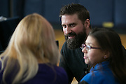 Pastor Chris Holdridge speaks with guests before a service at the Community Place of Greater Rochester on Sunday, December 18, 2016.