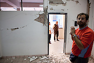 Gabriele Guerrini inspects damage inside a Mexicali classroom while school staff stand outside. A group of researchers led by Dr. Benson Shing, Vice Chair of the Department of Structural Engineering at the University of California, San Diego, inspected the earthquake damage in Mexicali, Mexico, April 7, 2010. A 7.2 magnitude earthquake in Baja California on Easter Sunday was felt as far away as Los Angeles.