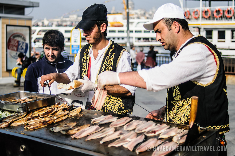 Cooking fish on an open grill on the waterfront of Eminonu in Istanbul near the Galata Bridge spanning the Golden Horn.