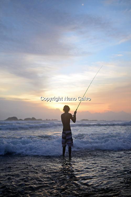 Young boy fishing on Hikkaduwa beach at sunset, Sri Lanka