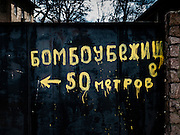 15 of April 2015 / Petrovski/ Donetsk Oblast/ Ukraine - Paint on a house door helping people to locate the bunkers. in English: Bomb shelter, 50 meters on the left.