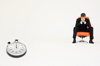 Worried businessman sitting on chair with stopwatch representing loss of time