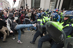 "© under license to London News Pictures. 25/03/2011: Masked protesters fight with police in riot gear on Regent Street during a day of protests. One protester kicks out at the police line. Credit should read ""Joel Goodman/London News Pictures""."