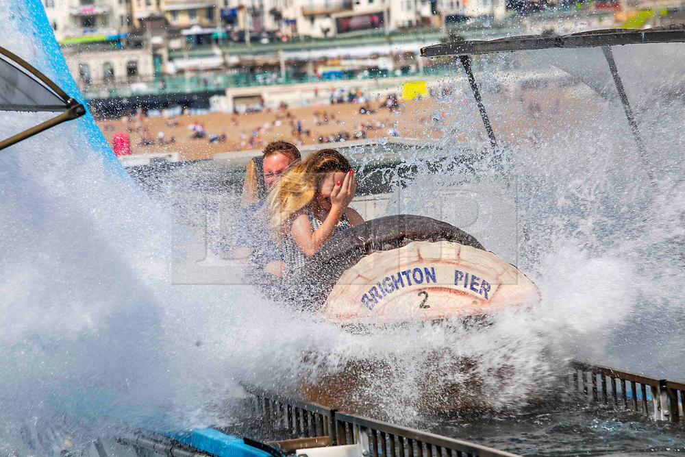 © Licensed to London News Pictures. 21/07/2016. Brighton, UK. Few people take ride  on the Big Spash water attraction on Brighton Palace Pier as sunny and warm weather continues to hit the seaside resort. Photo credit: Hugo Michiels/LNP