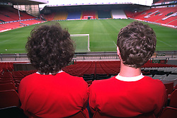 "LIVERPOOL, ENGLAND - 1996: John Power (R) and Peter ""Cammy"" Cammell  of band Cast sit on the Kop at Anfield, home of Liverpool FC. (Pic by David Rawcliffe/Propaganda)"