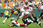 GREEN BAY, WI - SEPTEMBER 25:  Fullback William Henderson #33 of the Green Bay Packers goes airborne on a running play and gets tackled by linebacker Shelton Quarles #53 of the Tampa Bay Buccaneers at Lambeau Field on September 25, 2005 in Green Bay, Wisconsin. The Buccaneers defeated the Packers 17-16. ©Paul Anthony Spinelli *** Local Caption *** William Henderson;Shelton Quarles