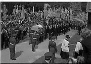 Funeral of Eamon DeValera.   (J72)..1975..02.09.1975..09.02.1975..2nd September 1975..Today saw the funeral of Eamon DeValera. He was laid to rest beside his wife Sinead in Glasnevin Cemetery,Dublin. Dignitries from all around the world attended at the funeral...The Tricolour draped coffin of Eamon DeValera is ceremonially carried to the graveside by military personnel.Picture shows the mourners taking up every available vantage point.