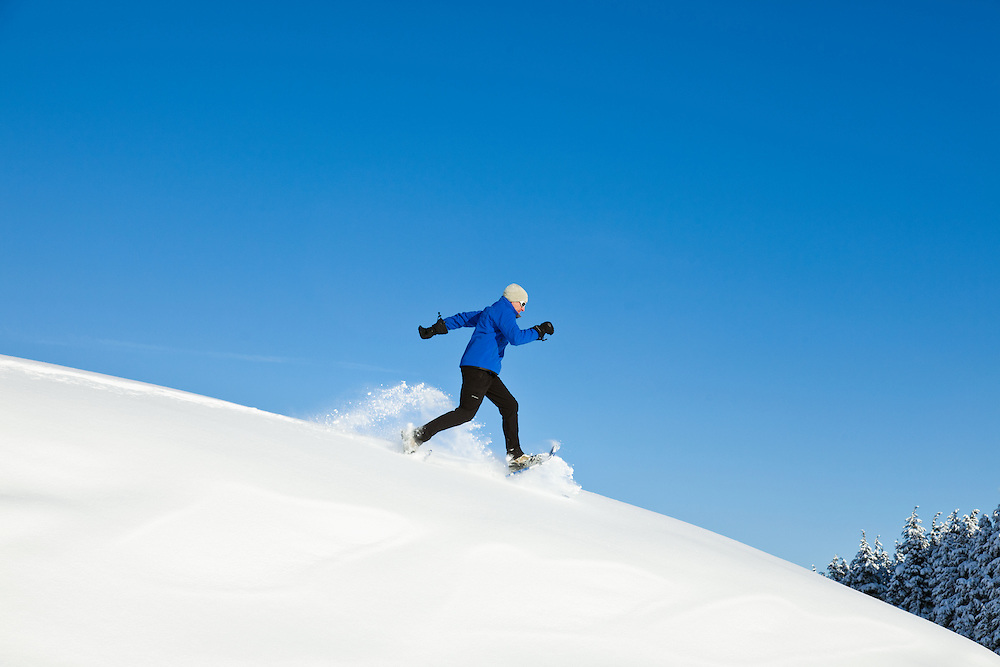 A hiker on snowshoes runs down a hill of powdery snow on a sunny blue-sky day at Turnagain Pass in the Chugach National Forest of Southcentral Alaska. Winter. Afternoon. MR.