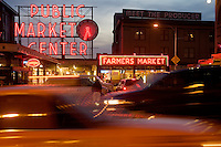 Traffic blurs past the Pike Street Market in Seattle, WA, USA at dusk.