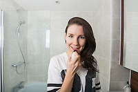Portrait of young woman applying lipstick in bathroom