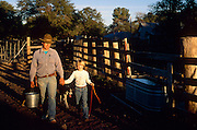 David Salge and daughter Nancy Salge walking along wooden corral, Vera Earl Ranch.©1991 Edward McCain. All rights reserved. McCain Photography, McCain Creative, Inc.