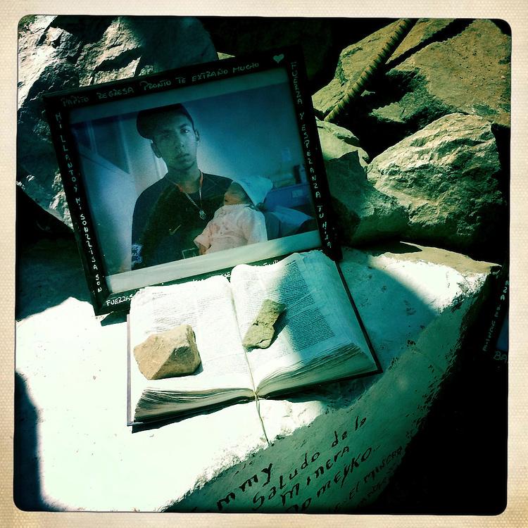 """Un retrato del minero Jimmy Sanchez junto a una biblia permanece sobre una roca en el campamento Esperanza. Plan B, es un ensayo fotografico basado en aquellas cosas que la mirada somera no permite ver, de los días de espera, angustia, soledad y fe que las familias de los 33 hombres atrapados en la mina San Jose dejaron en el paisaje arido del desierto de Atacama tras el esperado rescate. """"Plan B"""", tambien es un acto de fe personal, por intentar plasmar en un relato diferente, sin más pretensión que la mirada interna a los sentimientos que esa montaña atrapó implacable y para siempre, pero que bajo la mirada superficial de los medios no permite escudriñar por tratarse de pequeños fragmentos que apelan a emociones individuales y no a la masividad que persiguen los reportes de prensa. Este ensayo es una invitación abierta a descubrir los pequeños milagros que florecieron en la montaña y en el día a día de cada una de las familias que nunca dejaron de creer en la vida, aun así se enfrentaran a la inmensidad del desierto y a las minimas espectativas de vida que el lugar entregaba.""""Plan B"""", esta constituido por fotografías ejecutadas en su totalidad con un telefono iPhone 4 y la aplicacion Hipstamatic. ROBERTO CANDIA / REVISTA NUESTRA MIRADA"""