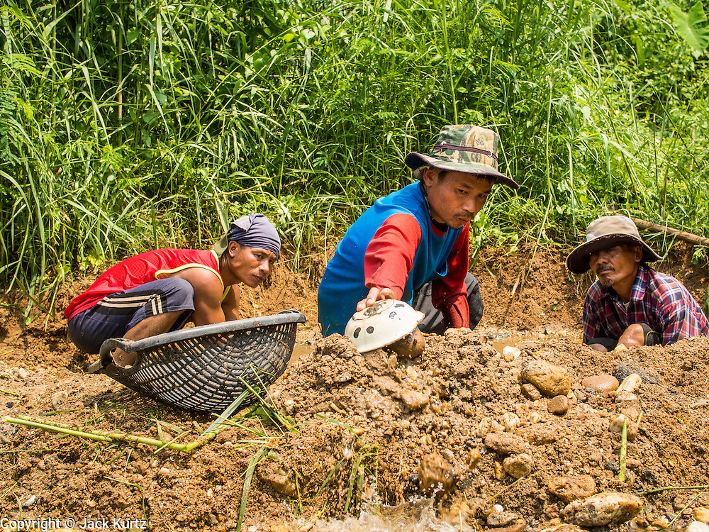 "22 APRIL 2014 - WANG NUA, LAMPANG, THAILAND: Artisanal gold miners dig a new mine on the banks of Mae Wang. Villagers in the Wang Nua district of Lampang province found gold in the Mae Wang (Wang River) in 2011 after excavation crews dug out sand for a construction project. A subsequent Thai government survey of the river showed ""a fair amount of gold ore,"" but not enough gold to justify commercial mining. Now every year when the river level drops farmers from the district come to the river to pan for gold. Some have been able to add to their family income by 2,000 to 3,000 Baht (about $65 to $100 US) every month. The gold miners work the river bed starting in mid-February and finish up  by mid-May depending on the weather. They stop panning when the river level rises from the rains. This year the Thai government is predicting a serious drought which may allow miners to work longer into the summer.    PHOTO BY JACK KURTZ"