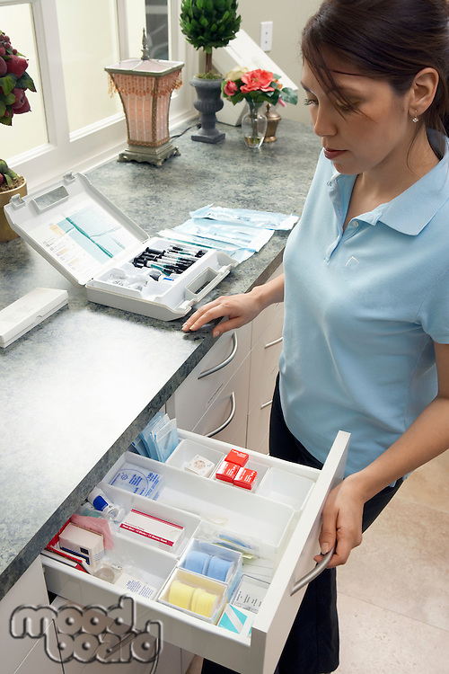 Dental Hygienist Looking in Supply Drawer