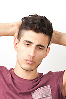Pensive young Middle Eastern man with hands behind head over white background