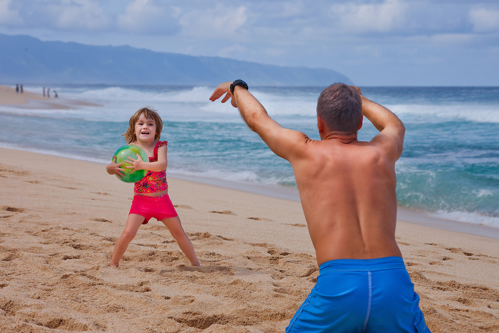 A little girl trimuphantly catchs a ball her father has trrown on the beach in Hawaii