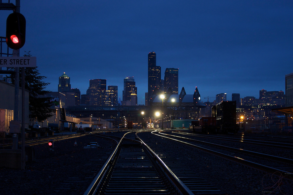 Train crossing at Lander St btwn Occidental & 3rd Ave, south of downtown (sodo) in Seattle, looking towards the downtown skyline with the SAFECO field straight ahead and the gleaming lights shining off the track