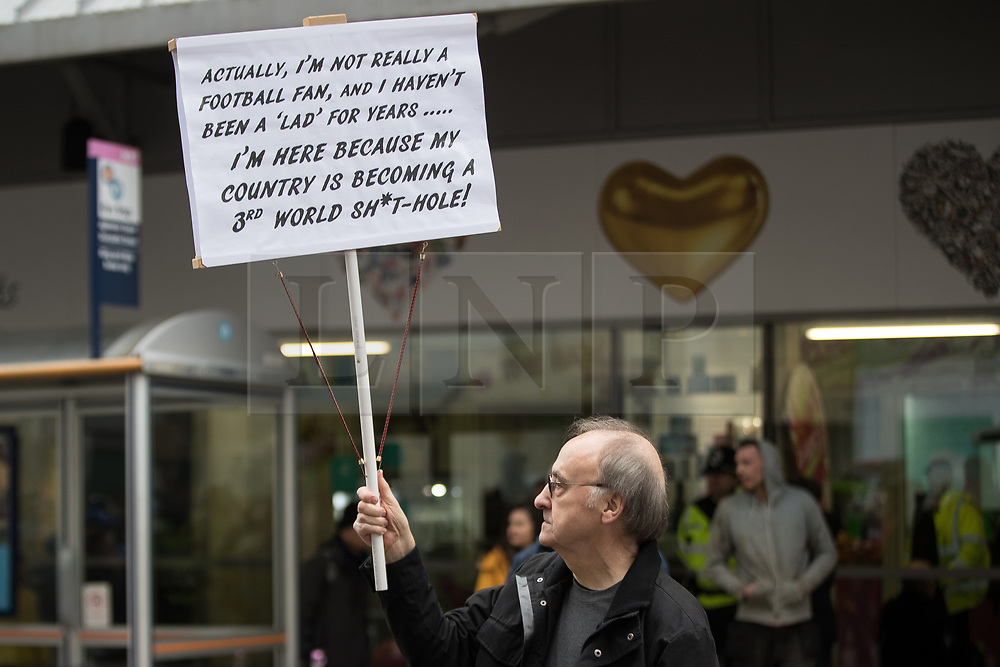 "© Licensed to London News Pictures . 24/03/2018. Birmingham, UK. A man holds a placard reading "" Actually I'm not really afootball fan and I haven't been a lad for years . I'm here because my country is becoming a third world shit-hole "" at a Football Lads Alliance demonstration against Islam and extremism in Birmingham City Centre . Offshoot group, The True Democratic Football Lads Alliance, also hold a separate demonstration . Photo credit: Joel Goodman/LNP"