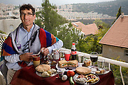 Ofer Sabath Beit-Halachmi, a Reform rabbi wearing a tall (prayer shawl), on the balcony of his home in Tzur Hadassah with his typical day's worth of food. (From the book What I Eat: Around the World in 80 Diets.) The caloric value of his typical day's worth of food in the month of October was 3100 Kcals.  He is 43 years of age; 6 feet, 1 inch tall and 165 pounds. Ofer's town in the Judean Hills about 15 minutes southwest of Jerusalem is a communal settlement where residents lease land and houses from the state of Israel for a 99-year period. On Friday evenings Ofer leads the Shabbat service in a small portable building that is kindergarten by day and synagogue at night and on weekends. MODEL RELEASED.