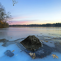 Lake Cochituate borders the Boston suburbs Natick, Wayland and Framingham and is part of the Cochituate State Park in Massachusetts. This peaceful New England winter photography image was captured on a quiet morning in January. The early morning light painted the New England scenery in beautiful colors and hues. A mixture of blue sky and the fading sunrise light and colors and the bolder surrounded by fallen memories of autumn provided perfect background and foreground elements for this Massachusetts nature photography image. I love experience the quietude that comes with an early morning photo shoot. <br />