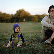 Clara Dews, 10 months, and her mom Sasha Dews sit on the cool grass adjacent to the Weaver's Way farm in Philadelphia, PA.  Photo by Lori Waselchuk. 2014.
