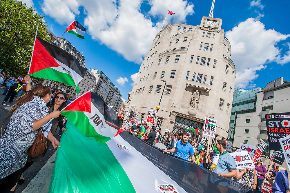 "Outside the BBC a huge flag is unfurled and as the march heads off peace signs alternate with pointing and chanting - Shame on you. Stop the 'massacre' in Gaza protest. A demonstration called by the Palestine Solidarity Campaign (PSC). They assembled at the BBC offices in Regent Street and marched to The US Embassy and on to a rally in Hyde Park. They called for ""Israel's bombing and killing to stop now and for David Cameron to stop supporting Israeli war crimes"". London, 09 Aug 2014."