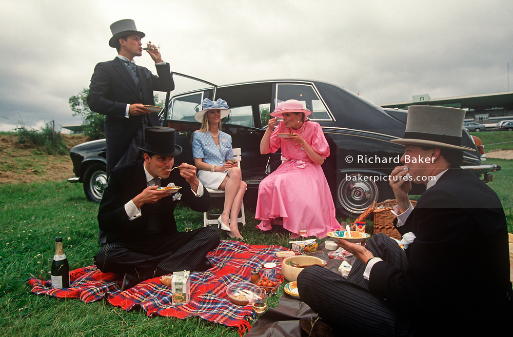 Royal Ascot racegoers picnic on the grass of an event car park, on 18th June 1992, in Ascot, England. Trays of food and two bottles of Champagne have been consumed during a break from betting and socialising. They are dressed in formal morning dress of top hat, waistcoat, tails with two of the men wearing red roses in their lapel button holes, all traditional and obligatory dress code in the Royal Enclosures which can be seen by visitors in the public car parks near the famous Berkshire race course. Royal Ascot is held every June and is one of the main dates on the sporting calendar and social season. (Photo by Richard Baker / In Pictures via Getty Images)