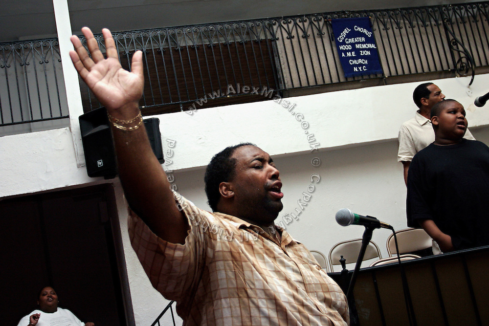 Rev. Ferguson, of the Music Ministry, and co-founder of the Hip Hop Church NY, is singing passionately along the Hip Hop Church Choir during a Mass Service at the Hip Hop Church in Harlem, New York, NY., on Thursday, June 22, 2006. A new growing phenomenon in the United States, and in particular in its most multiethnic city, New York, the Hip Hop Church is the meeting point between Hip Hop and Christianity, a place where ëGodí is worshipped not according to religious dogmatisms and rules, but where the ëHoly Spirití is celebrated by the community through young, unique, passionate Hip Hop lyrics. Its mission is to present the Christian Gospel in a setting that appeals to both, those individuals who are confessed Christians, as well as those who are not regularly attending traditional Services, while helping many youngsters from underprivileged neighbourhoods to feel part of a community, to make them feel loved and to help them not to give up when problems arise. The Hip Hop Church is not only forward-thinking but it also has an important impact where life at times can be difficult and deceiving, and where young people can be easily influenced for the worst purposes. At the Hip Hop Church, members are encouraged to sing, dance and express themselves in any way that the ëSpirit of Godí moves them. Honours to students who have overcome adversity, community leaders, church leaders and some of the unsung pioneers of Hip Hop are common at this Church. Here, Hip Hop is the culture, while Jesus is the centre. Services are being mainly in Harlem, where many African Americans live; although the Hip Hop Church is not exclusive and people from any ethnic group are happily accepted and involved with as much enthusiasm. Rev. Ferguson, one of its pioneer founders, has developed ëHip-Hop Homileticsí, a preaching and worship technique designed to reach the children in their language and highlight their sensibilities, while bringing forth Christianity. This ëKeep It Realí evangelism s