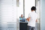 Man talking to woman standing in doorway of his office