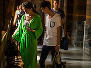 15 OCTOBER 2014 - BANGKOK, THAILAND:  Tourists make donations in Wat Pho in Bangkok. Women who don't dress modestly enough are asked to wear a green robe when they go into the chapel that houses the Reclining Buddha. The number of tourists arriving in Thailand in July fell 10.9 per cent from a year earlier, according to data from the Department of Tourism. The drop in arrivals is being blamed on continued uncertainty about Thailand's political situation. The tourist sector accounts for about 10 per cent of the Thai economy and suffered its biggest drop in visitors in June - the first full month after the army took power on May 22. Arrivals for the year to date are down 10.7% over the same period last year.   PHOTO BY JACK KURTZ