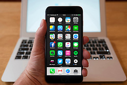 Detail of home page of large iPhone Plus smart phone with typical popular apps