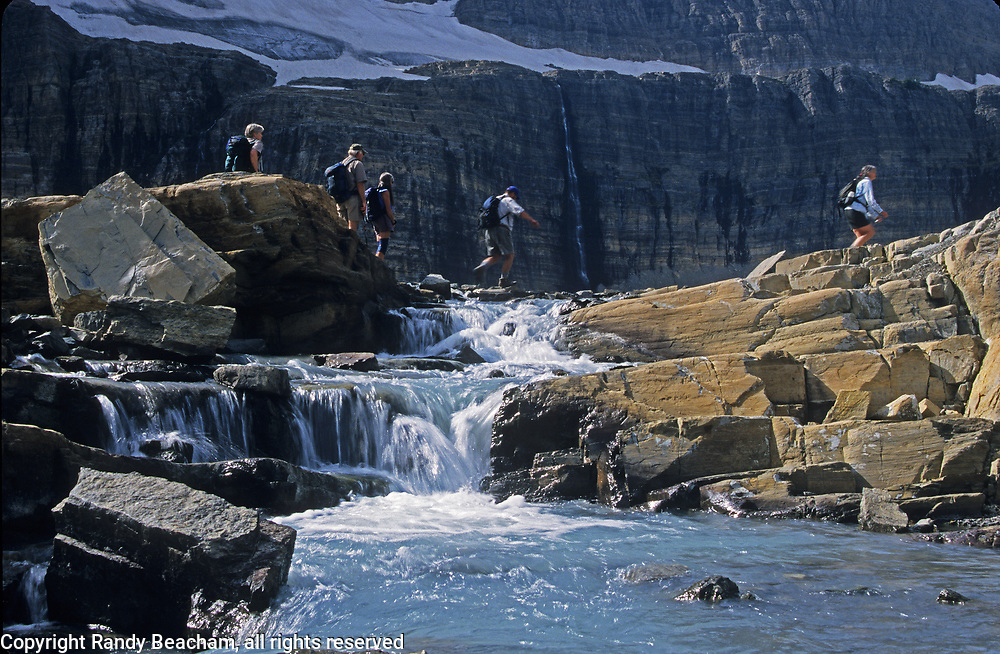 Hikers crossing glacier-fed stream at Grinnell Glacier, September 2002. Glacier National Park, northwest Montana.