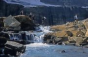 Hikers crossing glacier-fed stream at Grinnell Glacier, September 2002. Glacier National Park, northwest Montana.