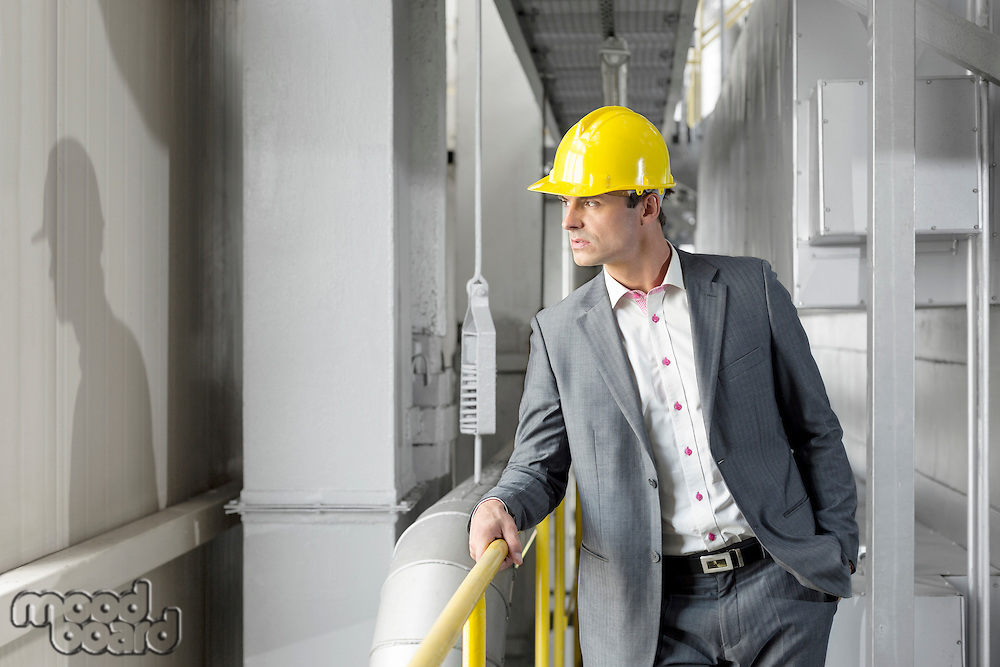 Young male manager wearing hard hat looking away in industry