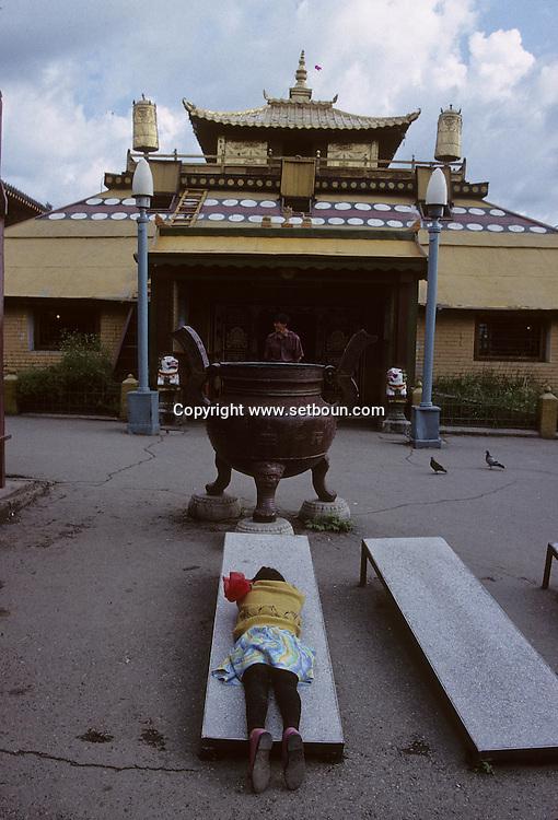 Mongolia. Ulaanbaatar. Gandan Monastery. Oulan Bator     / Monastère de Gandantegtchinlin à Oulan Bator . Mongolie.  Prosternation d'une jeune fille sur une planche à prière. L'un des actes religieux d'un croyant consiste à se prosterner devant un Stupa ou une statue religieuse ou encore devant une entree de temple (ici celui de TSOGTCHIN, precede par un ancien brûle-parfum) sur des planches ou une plaque de ciment prevues à cet effet, et selon un rituel bien precis. Tout d'abord, on joint les mains devant la poitrine puis on les elève au-dessus de la tête, pour les redescendre en touchant le front, le cou, la bouche et enfin la poitrine; ensuite on plie les genoux et on s'etale de tout son long, les bras bien en avant, tout le corps devant toucher le sol. Après quoi on se relève et on recommence plusieurs fois de suite les mêmes mouvements, qui ont une signification symbolique particulière pour exprimer le voeu que formule le croyant dans le but d'atteindre le rang d'un Bouddha.    119       P0002567